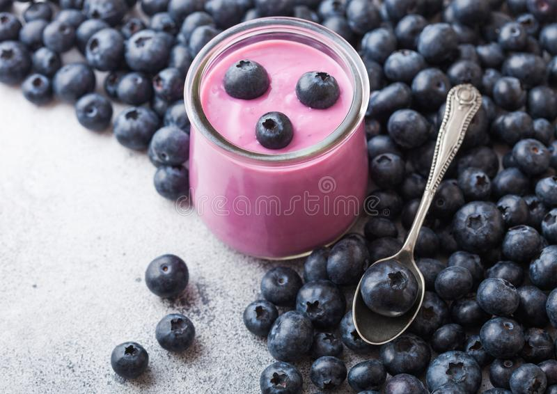 Fresh hommemade creamy blueberry yoghurt with fresh blueberries and silver spoon on stone kitchen table background. Fresh homemade creamy blueberry yoghurt with stock images