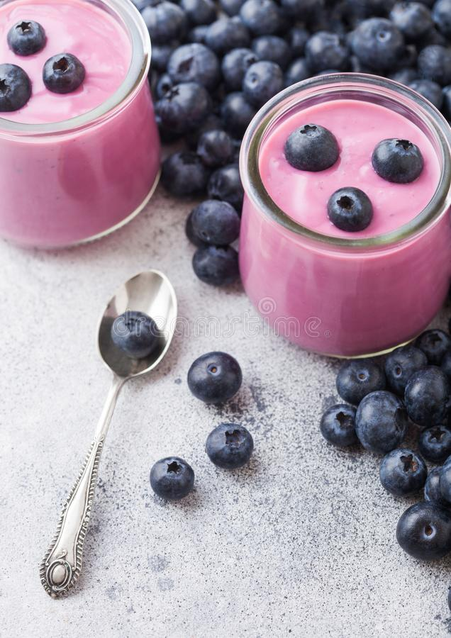 Fresh hommemade creamy blueberry yoghurt with fresh blueberries and silver spoon on stone kitchen table background. Fresh homemade creamy blueberry yoghurt with royalty free stock image