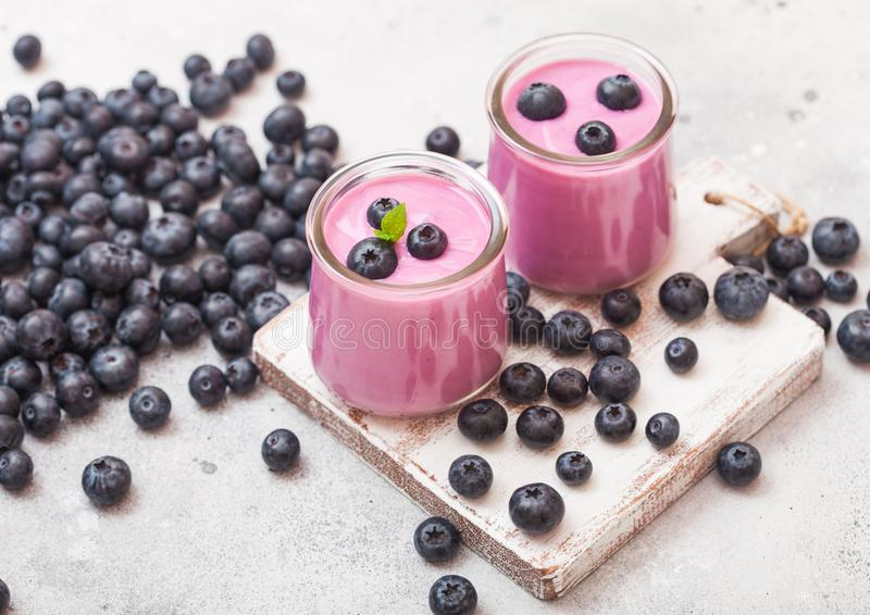 Fresh hommemade creamy blueberry yoghurt with fresh blueberries on vintage wooden board on stone kitchen table background. Fresh homemade creamy blueberry stock photo