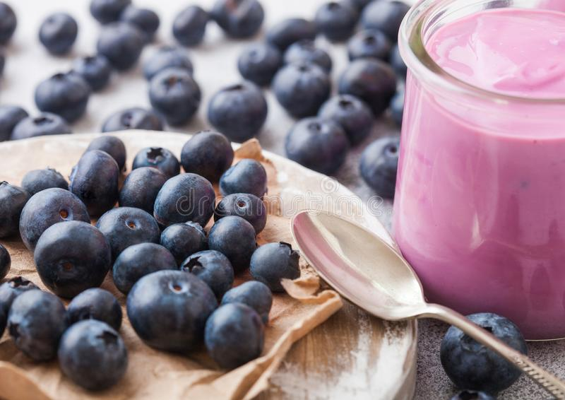 Fresh hommemade creamy blueberry yoghurt with fresh blueberries on vintage wooden board and silver spoon on stone kitchen table ba. Fresh homemade creamy stock photography