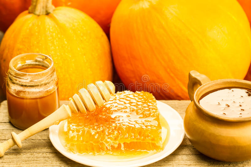 Fresh honey and drizzler on a wooden background. Autumn style, honeycomb, pumpkin stock images