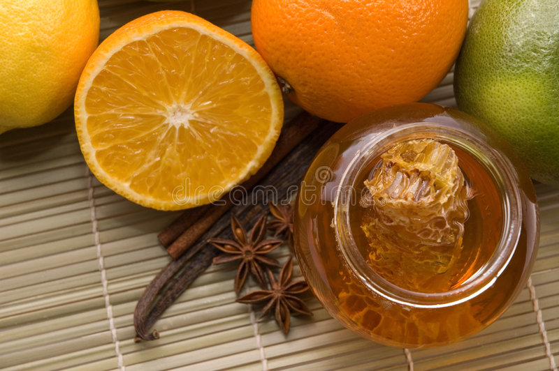 Fresh honey with honeycomb, spices and fruits royalty free stock images
