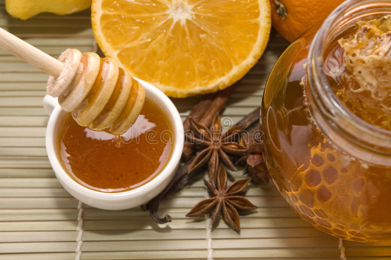 Fresh honey with honeycomb, spices and fruits stock photography