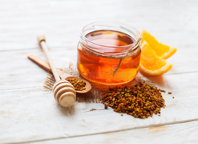 Fresh honey on wooden table. Honey in a glass jar and orange on a white background wooden rustic . Selective focus royalty free stock images