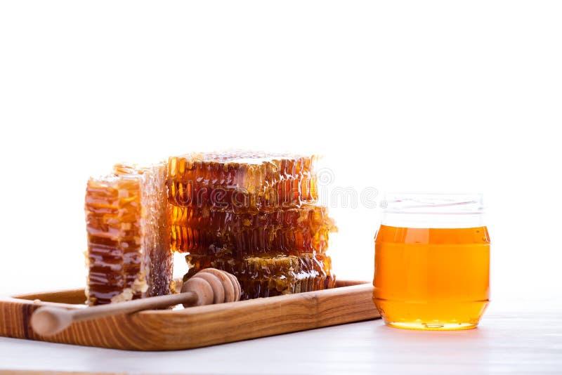Fresh honeycomb and honey dipper on white background stock image