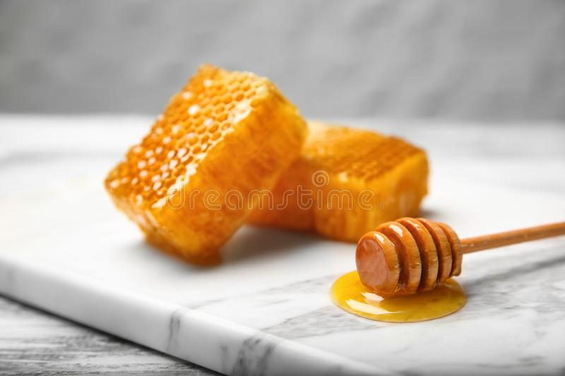 Fresh honeycombs and wooden dipper on marble board stock photos