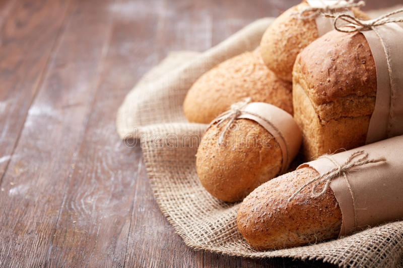 Fresh hot bread in a linen towel on a brown wooden table. free space for writing text. menu. advertising stock photo
