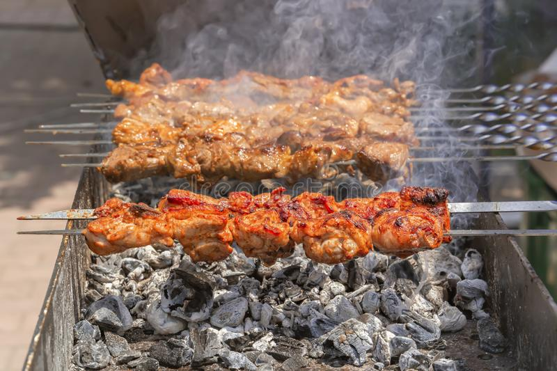 Fresh hot grilled chicken shish kebab barbecue on grid over coal with smoke. Close-up stock image
