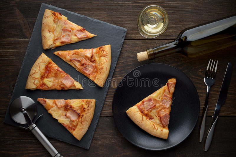 Fresh hot hawaiian pizza ready to eat with wine on wooden table. stock image