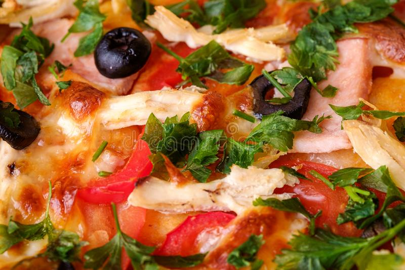 Fresh hot homemade pizza with chicken meat, ham, tomato, mozzarella cheese, black olives and parsley, macro view texture. For recipe book royalty free stock photography