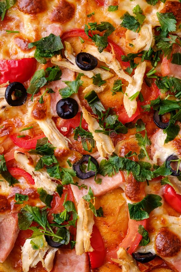 Fresh hot homemade pizza with chicken meat, ham, tomato, mozzarella cheese, black olives and parsley, top view texture. For recipe book stock photography