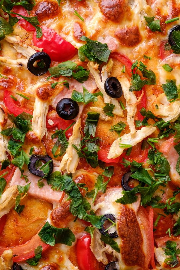 Fresh hot homemade pizza with chicken meat, ham, tomato, mozzarella cheese, black olives and parsley, top view texture. For recipe book royalty free stock photos