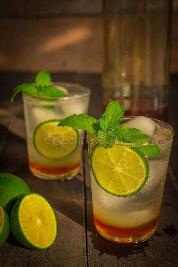 Fresh Ice Honey Lemon soda drink on the wood table there are lemon slice, same object and honey in glass bottle placed around. Close up royalty free stock image