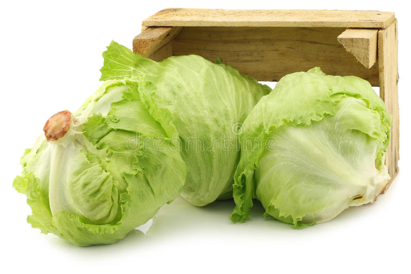 Fresh iceberg lettuce in a wooden crate. On a white background stock image