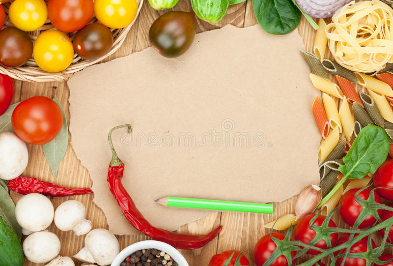 Fresh ingredients for cooking: pasta, tomato, cucumber, mushroom. And spices over wooden table background and paper with copy space royalty free stock images