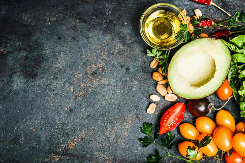 Fresh ingredients for salad or dip making: avocado, tomatoes,nuts,oil on rustic background, top view, place for text. Healthy food and cooking concept royalty free stock images