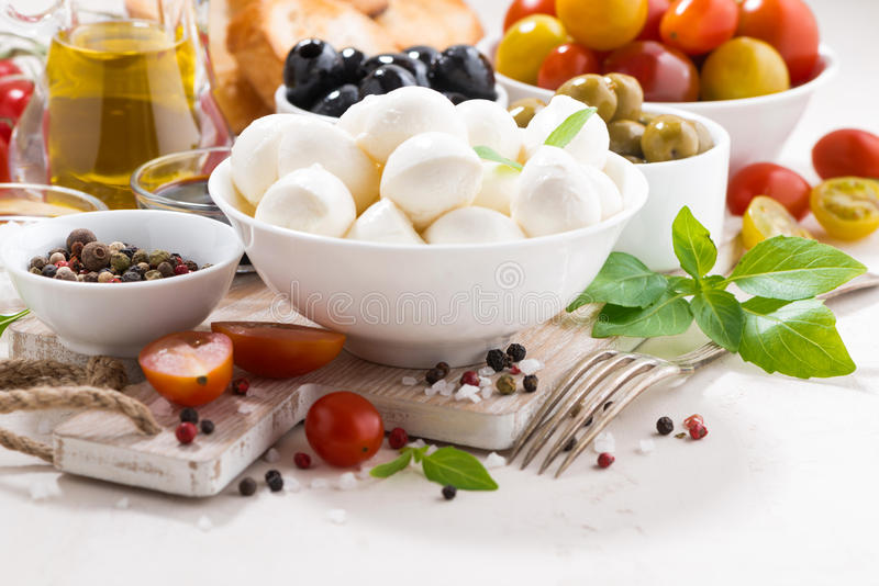 fresh ingredients for salad with mozzarella on white table stock images