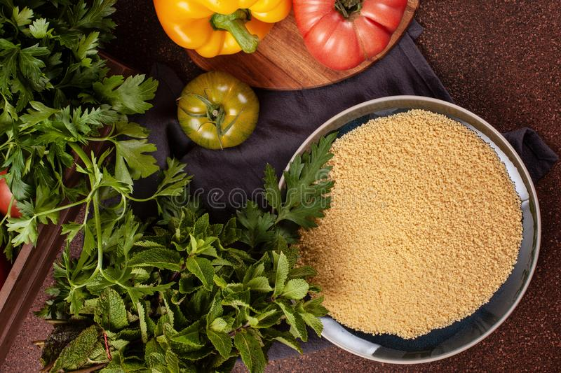 Fresh ingredients for tabbouleh salad: couscous, tomatoes, lemon, parsley, mint, olive oil, bell pepper. royalty free stock photography