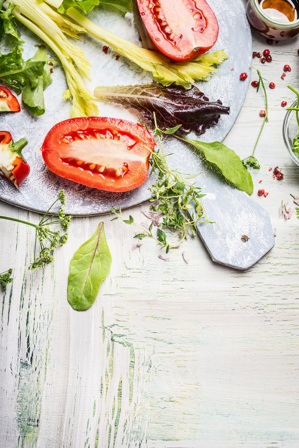 Fresh ingredients for tasty salad on round white cutting board and wooden background, top view. Place for text royalty free stock photo