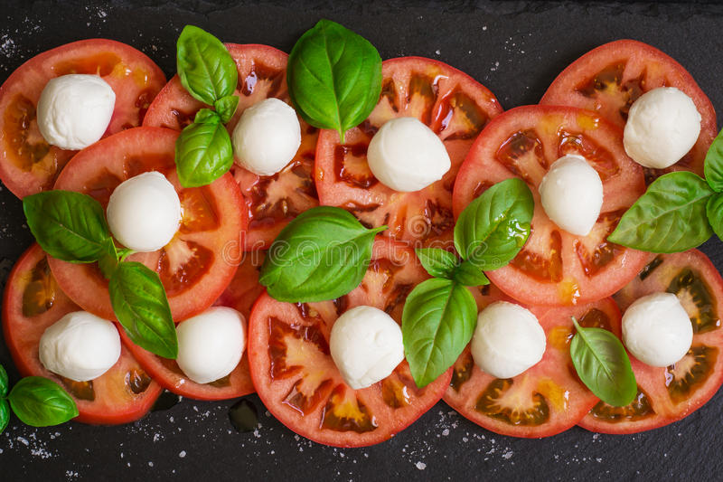 Fresh italian caprese salad on dark plate. Top view royalty free stock photos