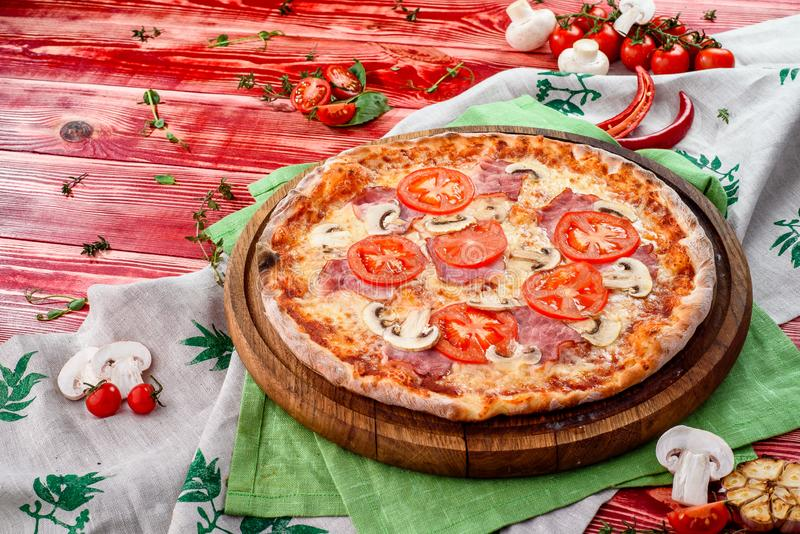 Fresh italian pizza with mushrooms, ham, tomatoes, cheese on wooden board, red rustic table. Copy space stock images