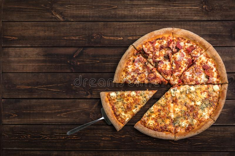 Fresh italian pizza and a pie spatula with one slice on the wooden background. Top view and copy space for text royalty free stock photography