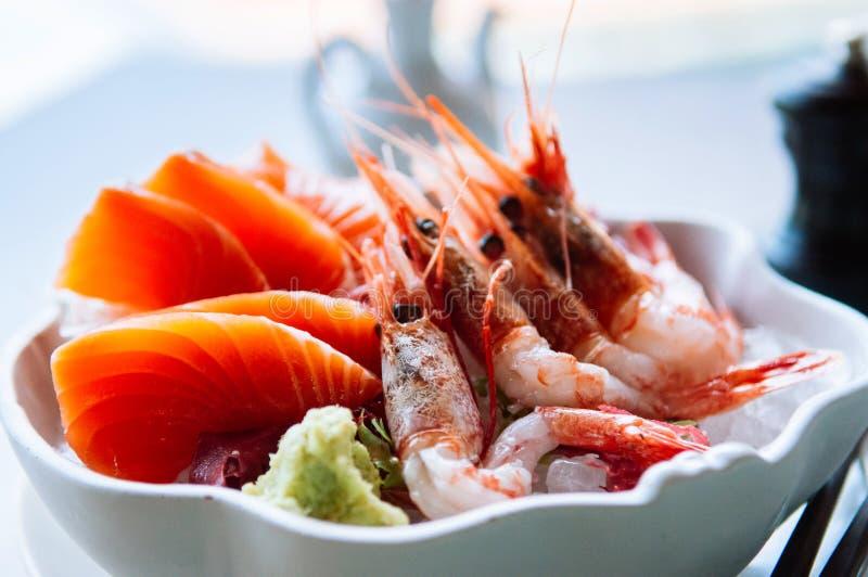 Fresh Japanese sashimi, raw salmon, sweet Ebi shrimps and wasabi. In white bowl. Close up shot stock photos