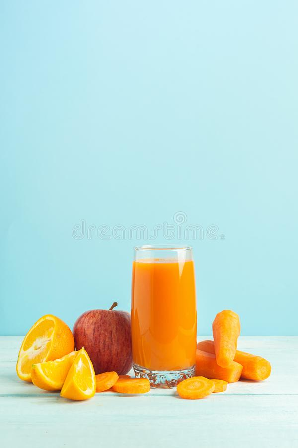Fresh juice from carrots and orange apples in a glass on a wooden blue background. Selective focus. Copy space stock photos