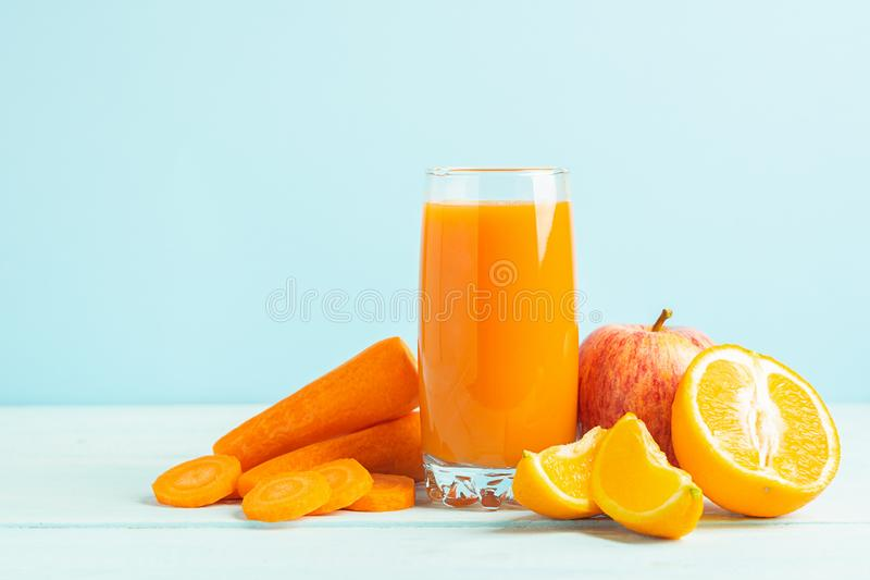 Fresh juice from carrots and orange apples in a glass on a wooden blue background. Selective focus. Copy space royalty free stock images