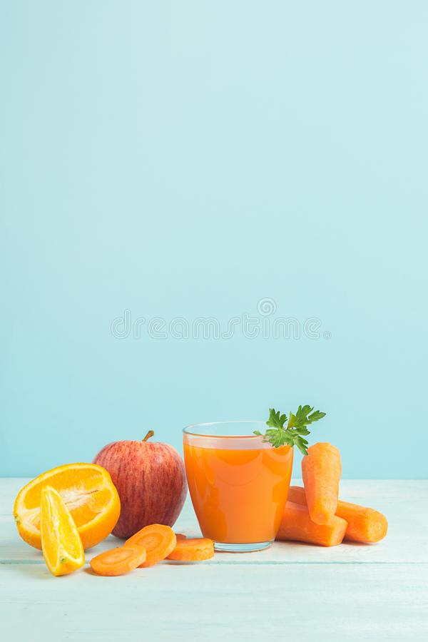 Fresh juice from carrots and orange apples in a glass on a wooden blue background. Selective focus. Copy space. royalty free stock photos
