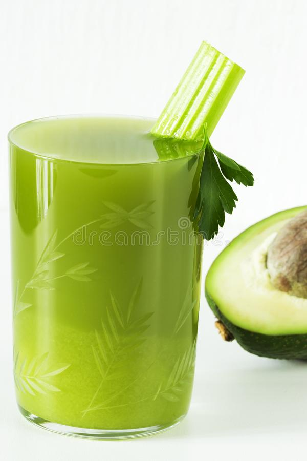 Fresh juice of celery and avocado, parsley in a glass Cup royalty free stock photo