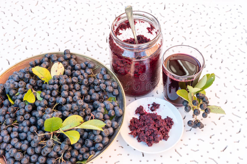Fresh juice and jam of black chokeberry Aronia melanocarpa in glass and berry in pot on white textured background. Fresh juice and jam of black chokeberry Aronia stock photo
