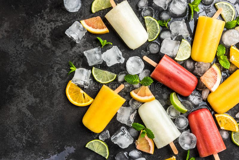 Fresh juice lolly pops over ice cubes. Background citrus cold colorful concept cool copyspace dark delicious dessert flat lay flavor flavored food freshness stock image