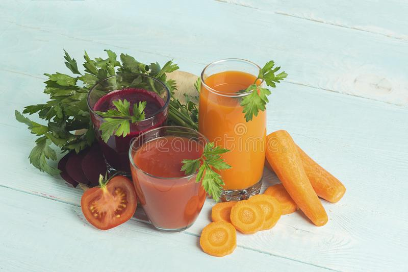 Fresh juice smoothies from a variety of vegetables beetroot apple carrot tomatoes in glasses on wooden blue background. stock photos