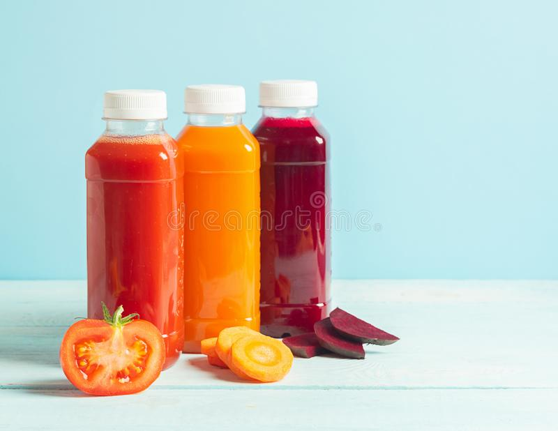 Fresh juice smoothies from a variety of vegetables carrots apple tomatoes beets in bottles on a wooden blue background. stock photo