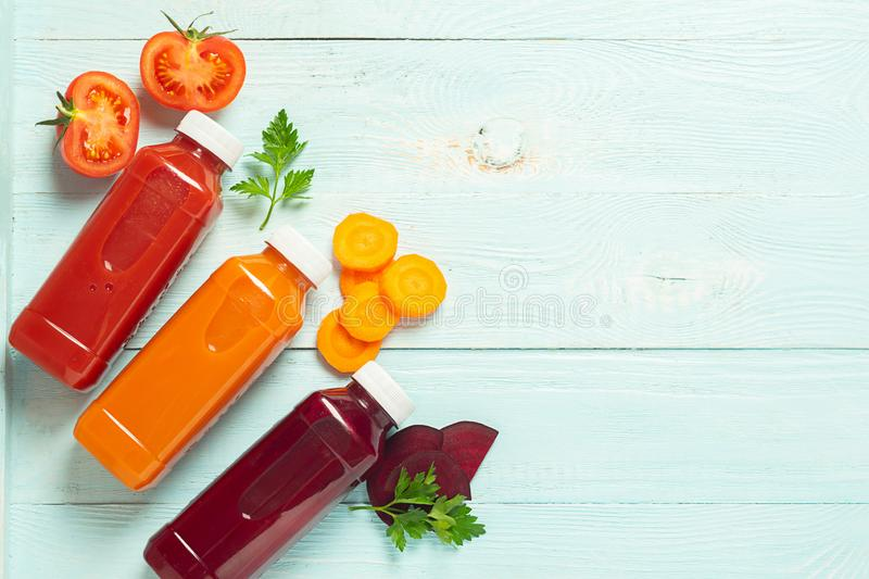 Fresh juice smoothies from a variety of vegetables carrots apple tomatoes beets in bottles on a wooden blue background. stock photos