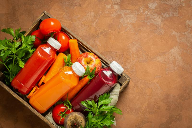 Fresh juice smoothies from a variety of vegetables carrots apple tomatoes beets bottles in wooden box brown background. stock photography