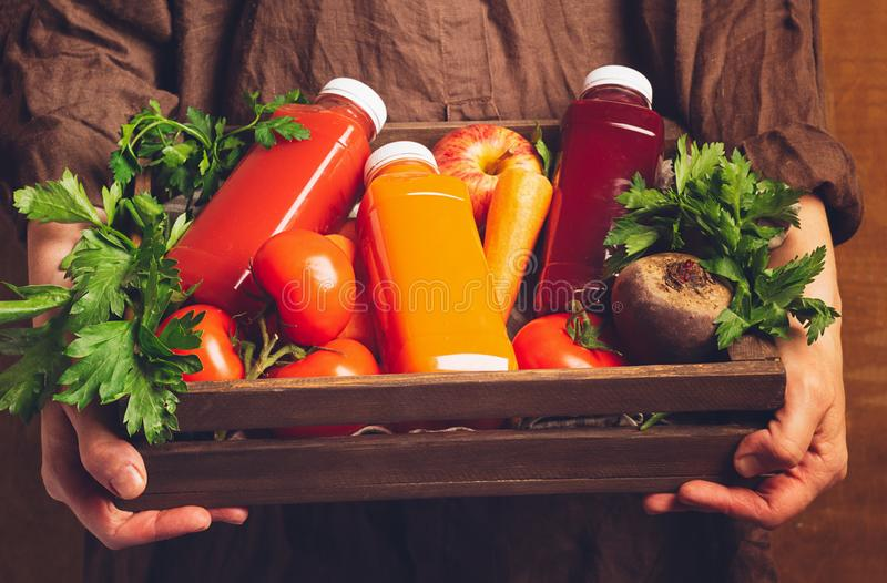Fresh juice smoothies from various vegetables carrot apple beet tomatoes in bottles in a wooden box in female hands. royalty free stock image