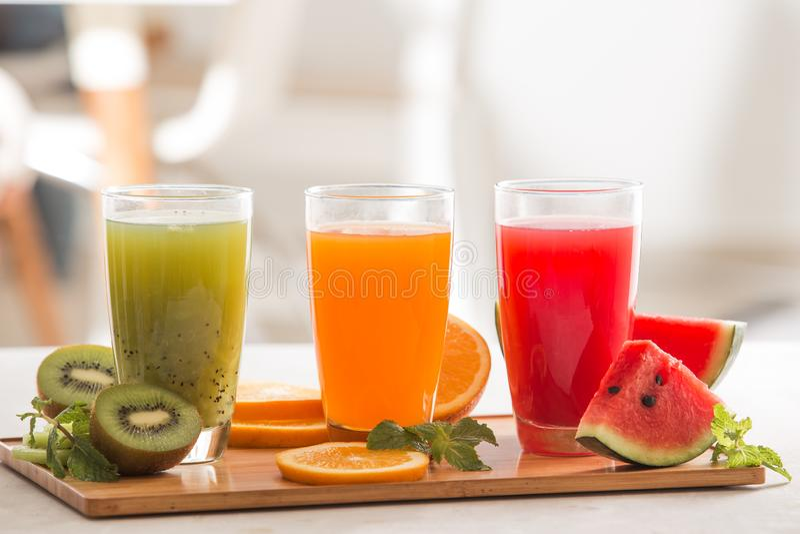 Fresh juices smoothie three glass red green orange tropical fruits water melon, kiwi, orange. Selective focus royalty free stock photo