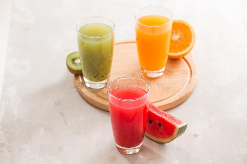 Fresh juices smoothie three glass red green orange tropical fruits water melon, kiwi, orange. Selective focus royalty free stock images