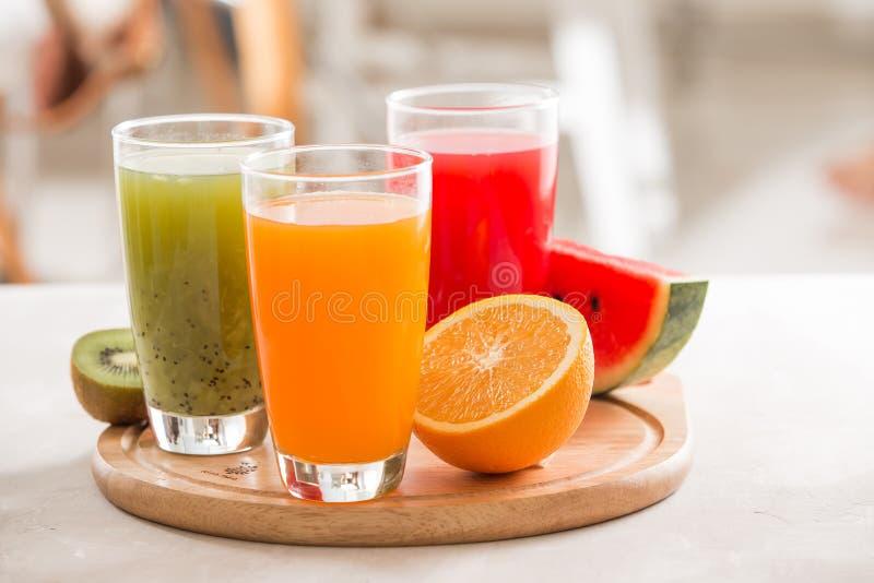 Fresh juices smoothie three glass red green orange tropical fruits water melon, kiwi, orange. Selective focus stock photography