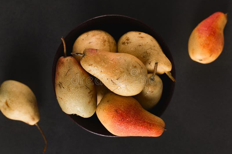 Fresh juicy appetizing pears in a brown bowl, summer concept, copy space stock photography