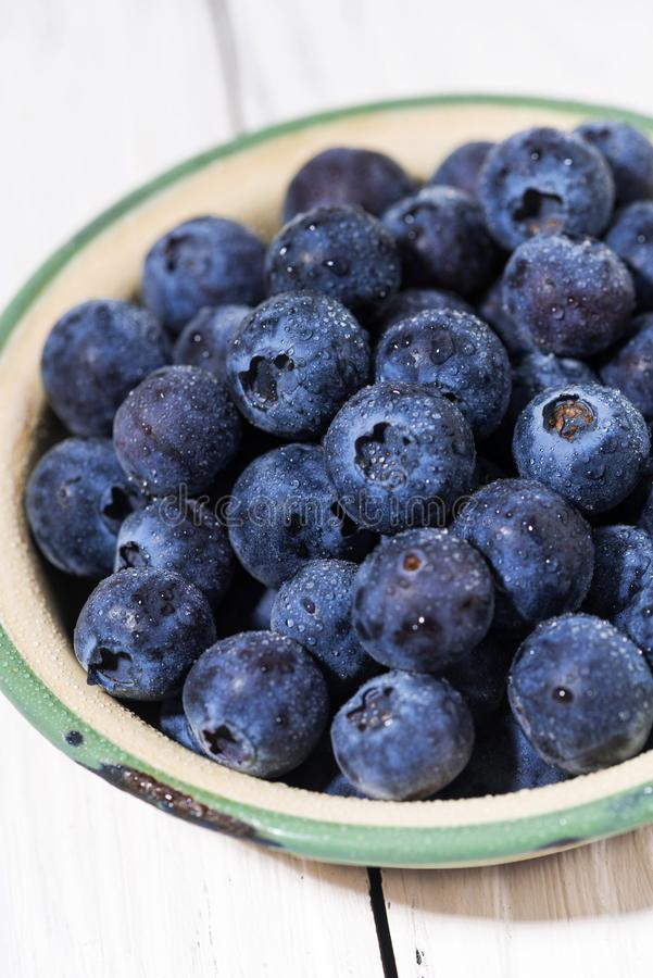 Fresh juicy blueberries in a bowl, vertical closeup royalty free stock images