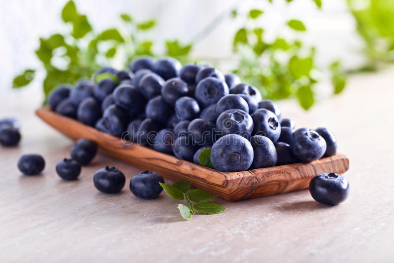 Fresh juicy blueberries with green leaves on a kitchen table . royalty free stock image
