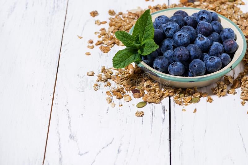Fresh juicy blueberries and homemade granola on white background royalty free stock image