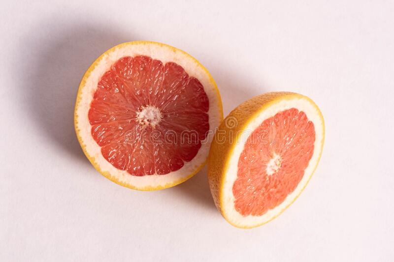Fresh, juicy and chopped two oranges. On a white plate background stock photo