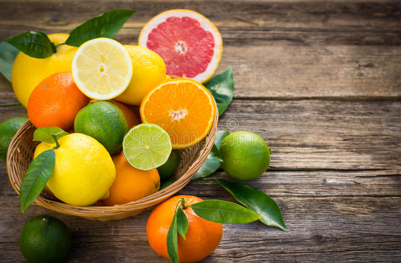 Fresh and juicy citrus fruits. In the basket on the rustic table royalty free stock photography