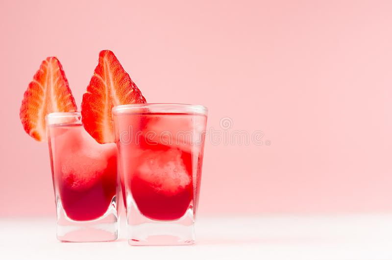 Fresh juicy cocktails in two shot glasses with ice cubes, strawberry slice in modern youth interior in pastel soft pink color. Fresh juicy cocktails in two shot royalty free stock image