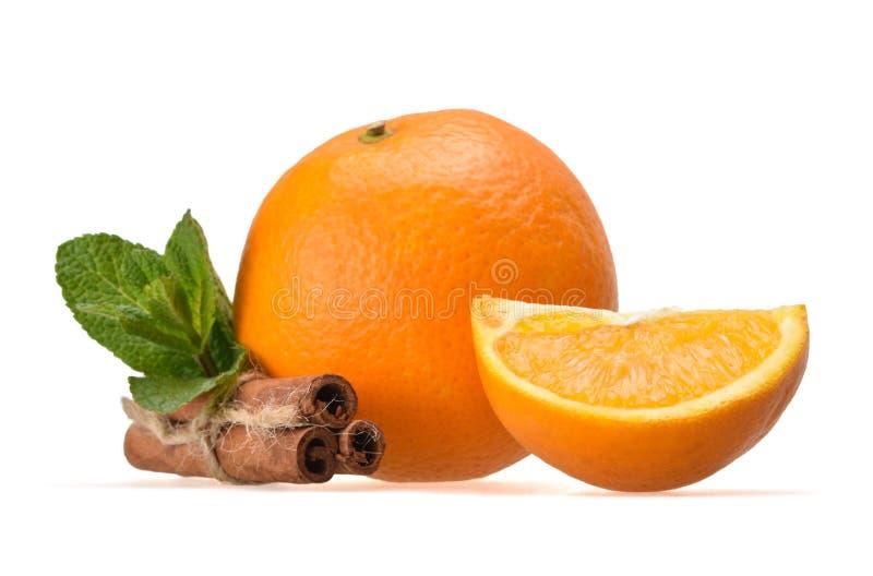 Fresh juicy composition of ripe orange, peppermint, small orange quarter and cinnamon sticks royalty free stock image