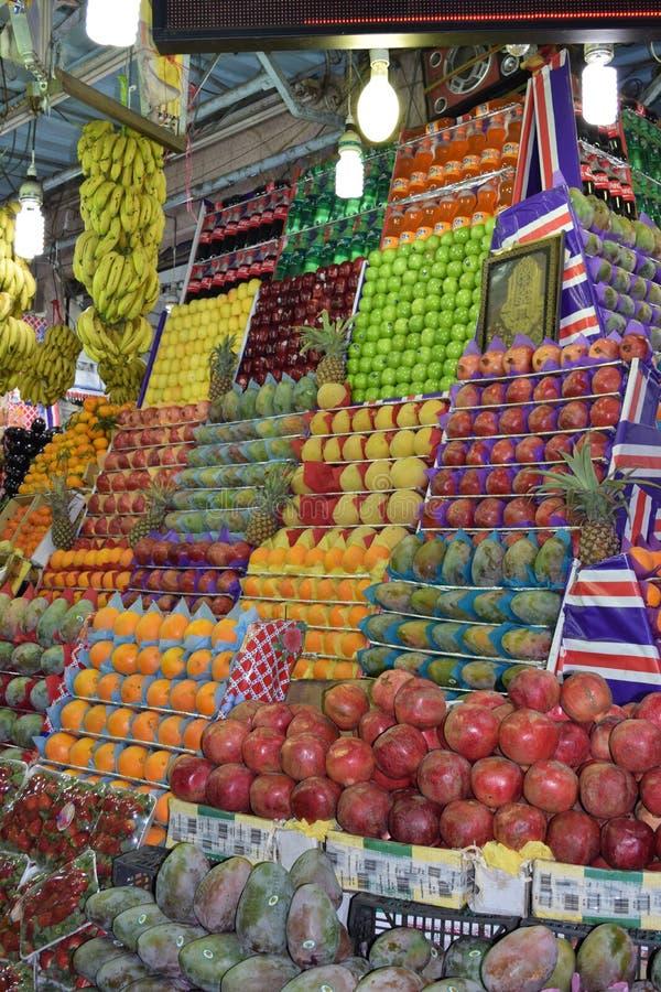 Fresh juicy fruits at the market: pomegranates, mangoes, apples, pineapples, bananas royalty free stock images